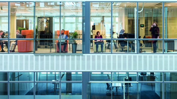 people working in an office in front of a glass facade Coor HQ